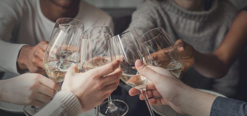 wine tasters cheers at table